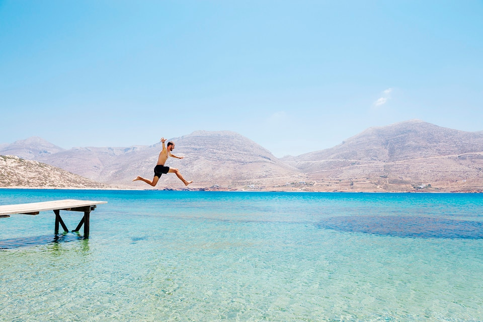 Man jumping from a wooden jetty in Greece