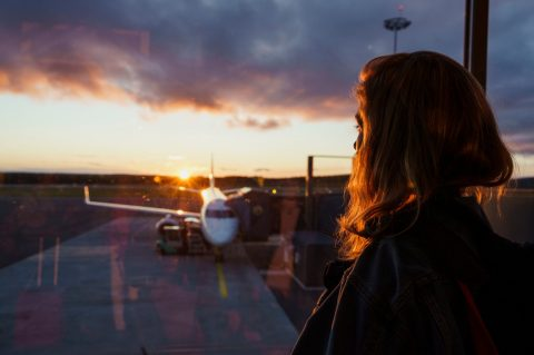 Woman staring out an airport window.
