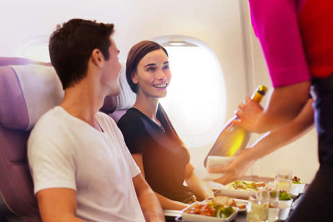 A flight attendant showcasing a bottle of white wine to customers during inflight meal service in Premium Economy