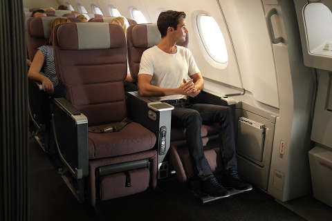 Man sitting in premium economy exit row