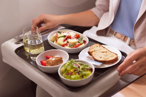 Premium Economy tray service with salad, bread and white wine.