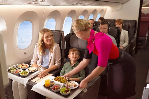 A flight attendant serving meals to a family in Premium Economy