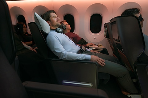 Man sleeping in premium economy seat