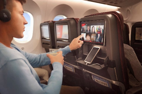 Dreamliner economy solo passenger watching entertainment screen