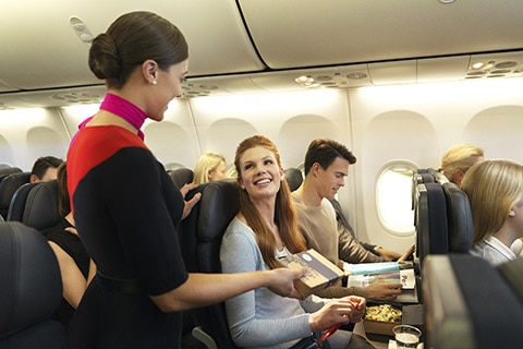 Cabin crew delivering female customer a packaged meal.