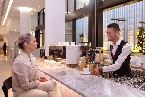 Lady being served an espresso at marble bar Qantas Perth transit lounge