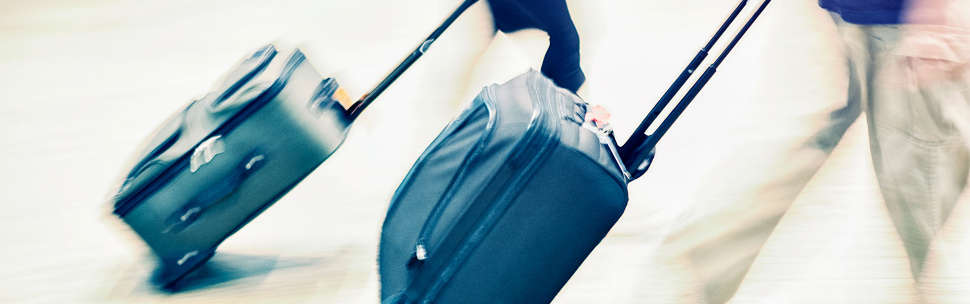 Man carrying suitcase through airport