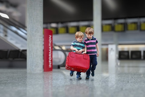 Children crrying luggage through the airport