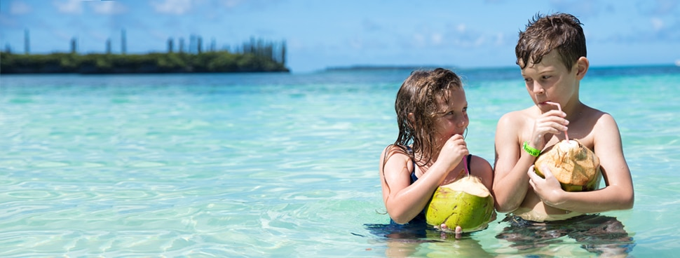 Kids on tropical beach drinking out of coconuts
