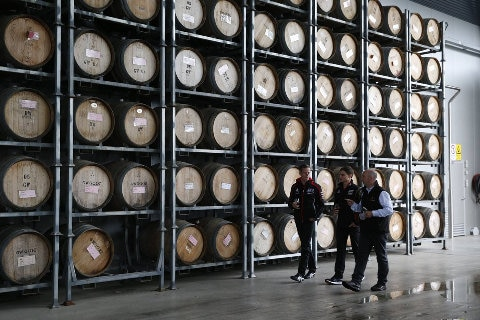 people walking past wine barrels