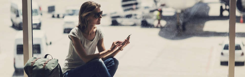 Airport guides - woman using smartphone in departure lounge