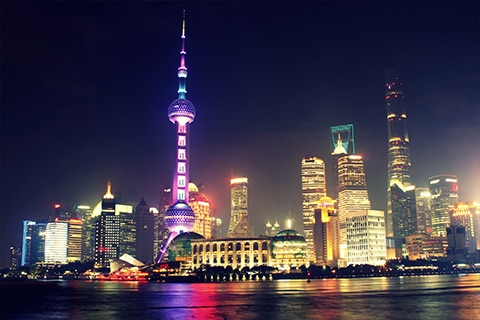 View of Shanghai at night with bright lights over the city