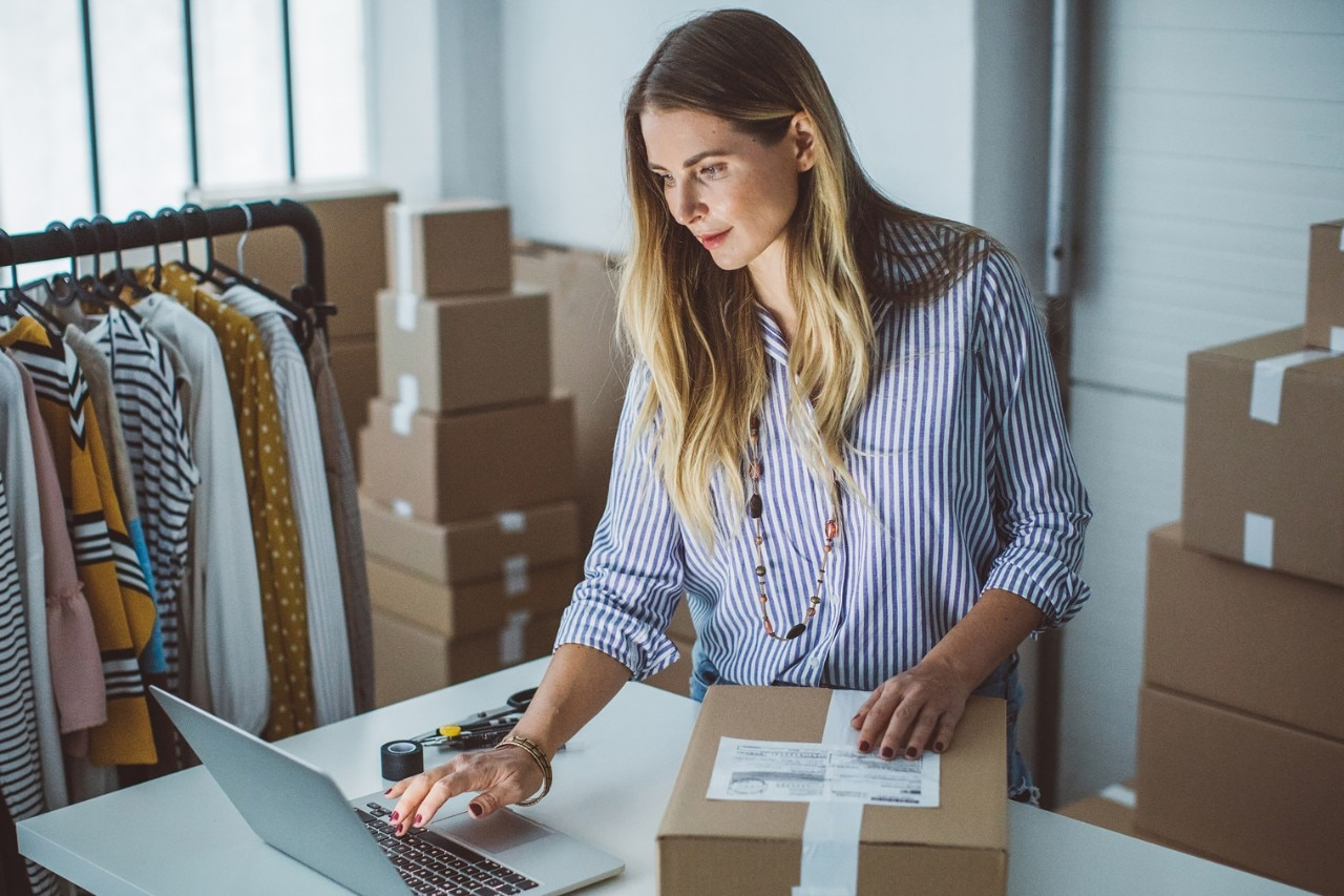 Small business woman sorting online clothing orders