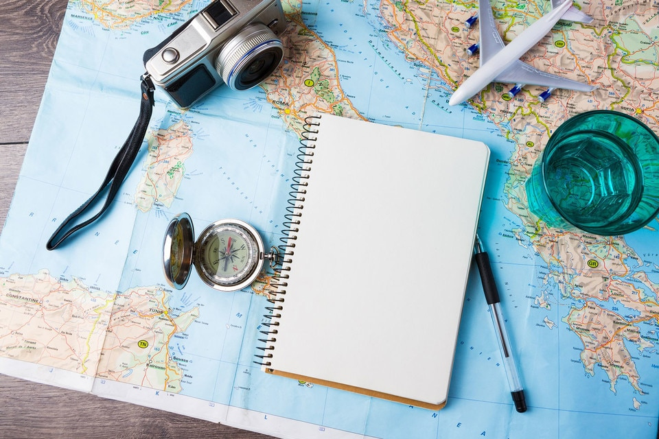 Holiday planning map, compass and camera