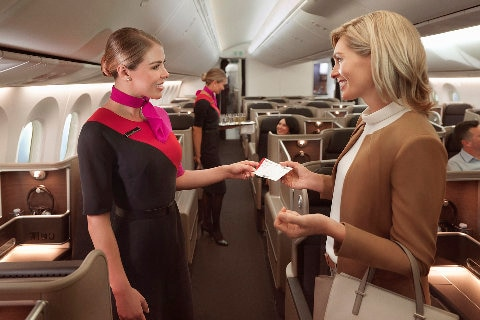 A cabin crew greets a female passenger in the Dreamliner International Business cabin