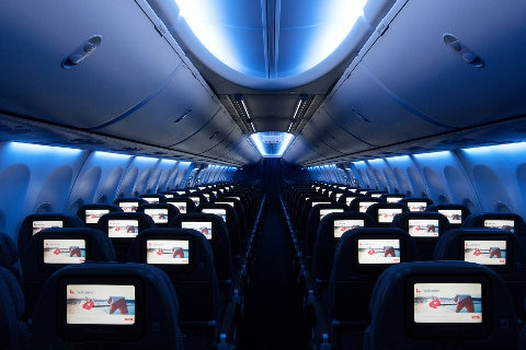Dimmed interior of aircraft cabin showing screens