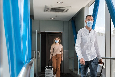 Customers boarding a flight wearing face masks