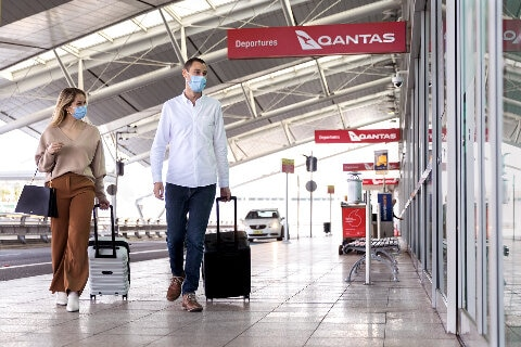 Customers entering the airport terminal wearing face masks