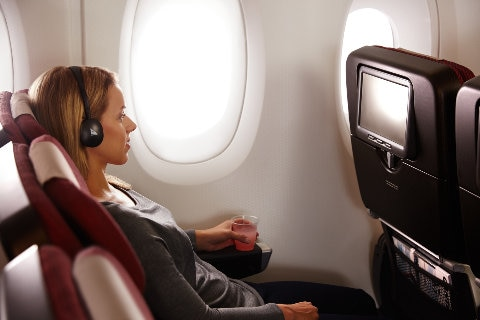 Qantas A380 Economy Cabin, lady reclined enjoying the inflight entertainment