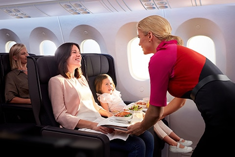 A flight attendant serving meals to a family travelling with a little girl in the Qantas 787-9 Dreamliner