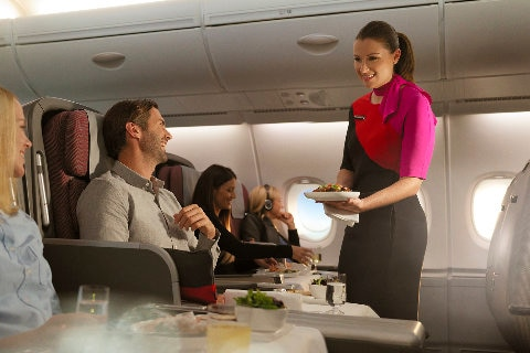 Qantas flight attendant serving a customer lunch in business class