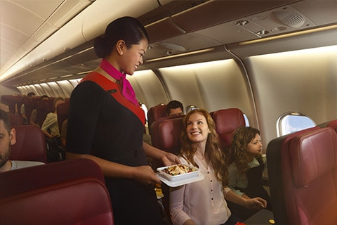 Lady being served inflight meal by cabin crew on A330