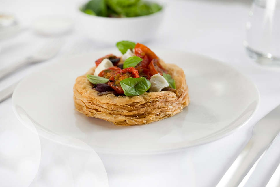 Caramelised onion tart with anchovy, roasted cherry tomatoes, goat