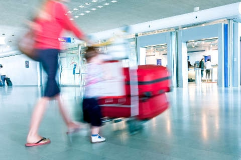 Lady with baggage trolley in terminal