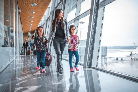 Mother walking with kids through the terminal