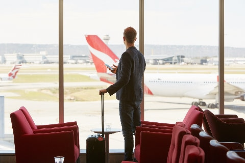 Man looking out window in Qantas lounge