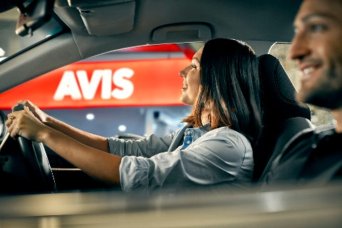Couple in car driving in front of Avis