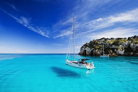 Boat sailing on crystal blue water
