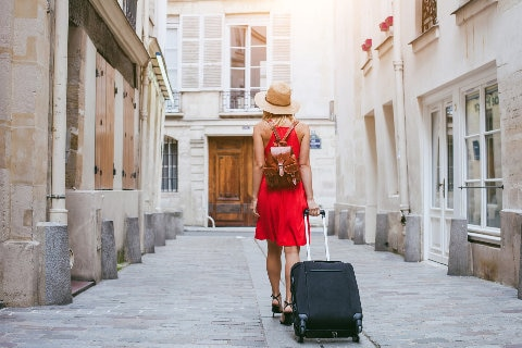 Lady walking with suitcase - Hotels and Airbnb