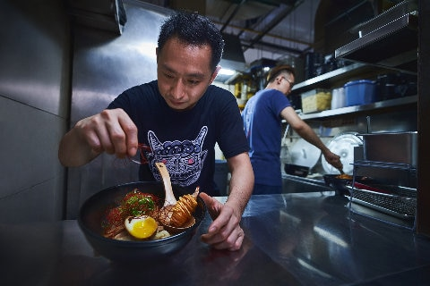 Chef serving Singapore noodles in a dish