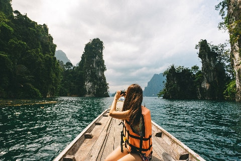 Tourist taking  photos in Thailand on a boat