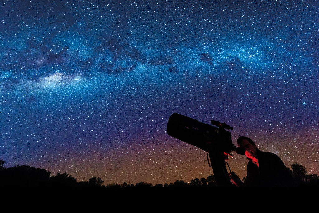 Telescope looking at night sky full of stars
