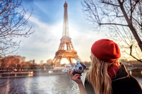 Girl in red cap holding camera