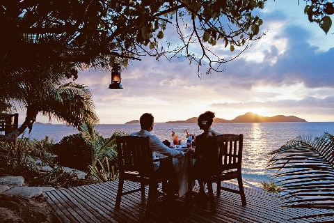 Couple sipping cocktails at sunset