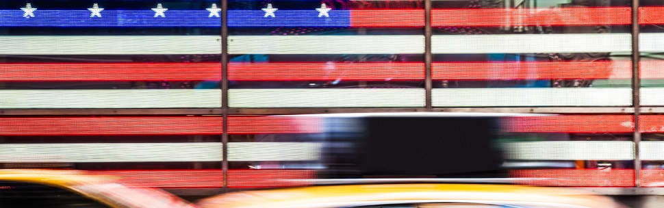 Yellow taxi infront of American flag