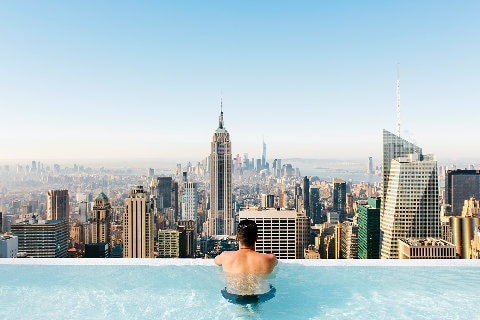 Man in pool looking over New York City
