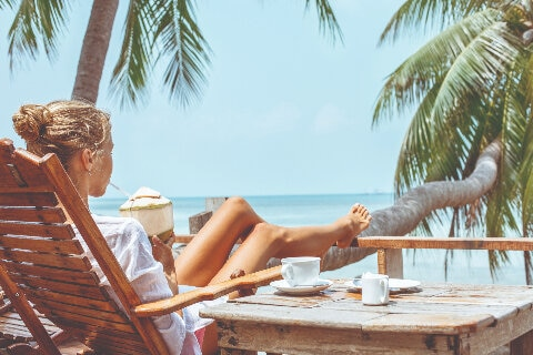 Women sitting on sun lounge drinking a coconut by the beach