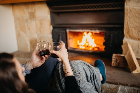couple in front of fire with red wine