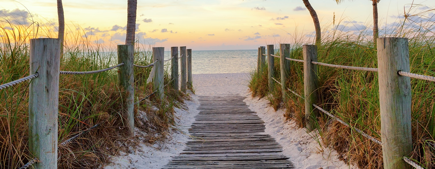 Footbridge leading to beach at sunset