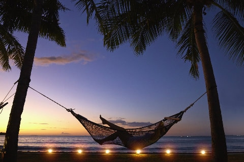 Silhouette of woman relaxing in a hammock at sunset