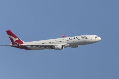 Qantas A330 flying over white clouds in blue sky