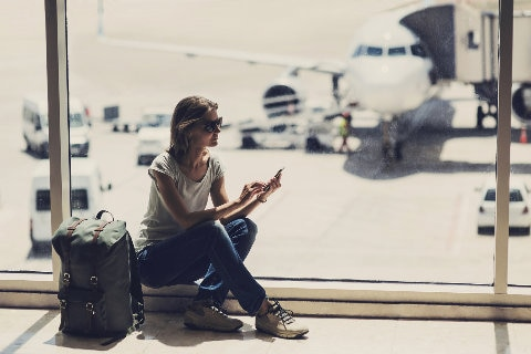 Women at airport on smartphone