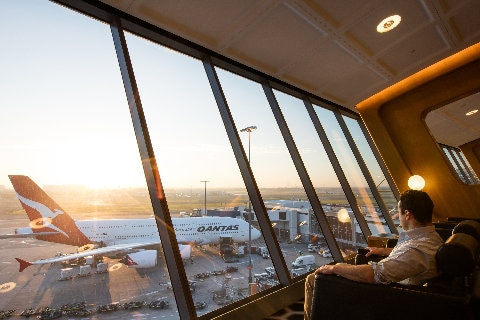Man looking out the window at the airport lounge