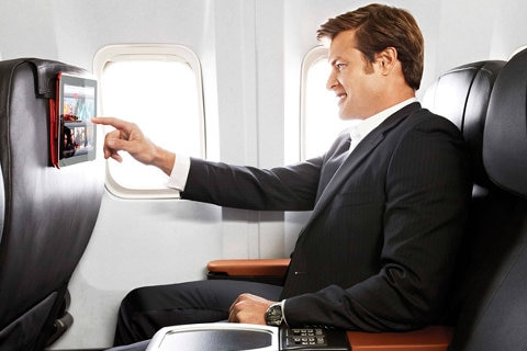Man on aircraft cabin watching a screen