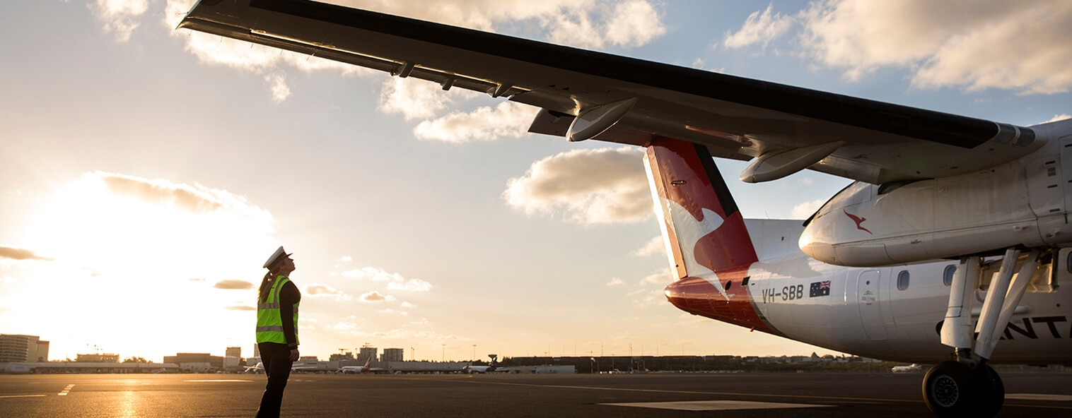 Qantas plane on tarmac with engineer